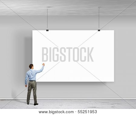 Image of businessman standing with back and writing on blank banner