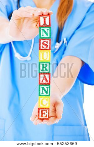 Midsection of nurse holding blocks spelling out insurance isolated over white background