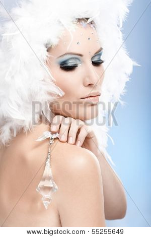 Luxurious beauty holding crystal jewel, wearing fancy makeup with strasses and white feather hat.