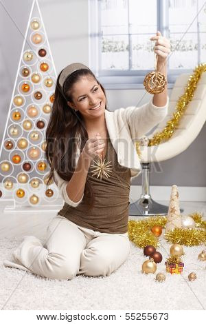 Laughing young woman preparing for christmas, selecting decoration design christmas tree in bright living room.