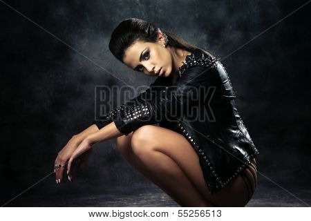 sexy brunette woman in black leather jacket  studio shot