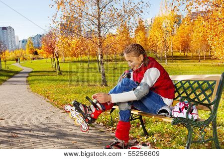 Putting On Skates On The Bench In The Park