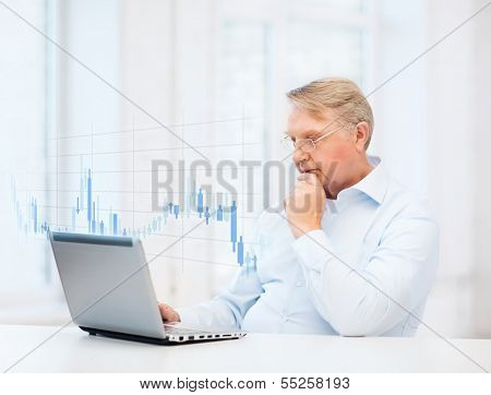 technology, money, oldness and business concept - old man in eyeglasses with laptop computer and forex chart at home