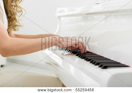 Close up view of hands playing piano. Concept of music and enjoyment