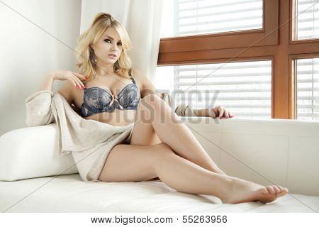 Beautiful and sexy young adult sensuality blonde woman in blue lingerie and brown sweater on the white sofa in window on luxury apartment