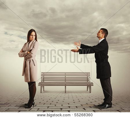 young man apologizing to woman at outdoor