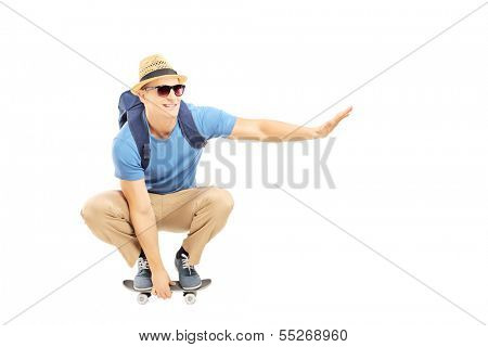 Smiling male student with backpack skating on a skate board isolated on white background