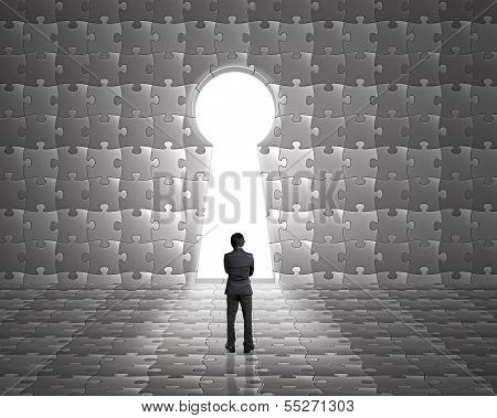 Businessman Stand Toward Key Hole Shape Door On Puzzles Wall With Bright Outside Background