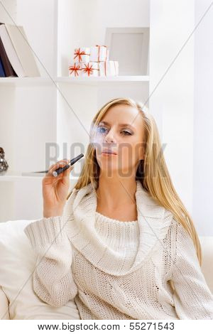 young beauty girl with e-cigarette  in light room