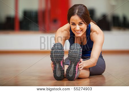 Happy woman warming up at a gym