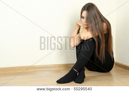 Lonely sad woman sitting on floor near wall