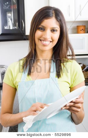 young woman drying dishes in kitchen