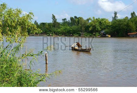 Wooden Row Boat Float On River That Enclosed By Green Trees
