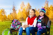 stock photo of 11 year old  - Two happy girls 11 years old sitting on the bench in autumn park with backpacks and coffee - JPG