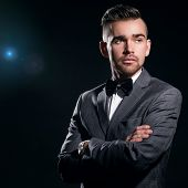 Portrait of a handsome man in a suit who is posing over a black background with a blue particles beh