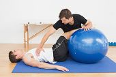 stock photo of chiropractic  - Physical therapist assisting young man with yoga ball in the gym at hospital - JPG