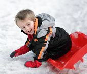 pic of toboggan  - Happy young boy out playing in the snow on his sledge - JPG