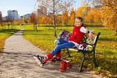 stock photo of 11 year old  - Happy blond 11 years old girl with amazing smile sitting on the bench wearing rollerblades and resting after skating in the autumn park on sunny day - JPG