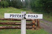 stock photo of log fence  - Rustic private road sign in country setting with road and fence - JPG