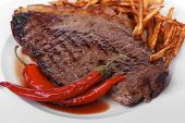 meat food : grill beef steak with potato chips and dry red hot chili peppers  on white round plate i