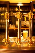 stock photo of spigot  - Luxury gold beer spigot at the brewery with a glass of beer - JPG