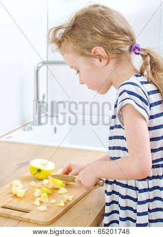 Little Girl Cutting Apple In The Kitchen.