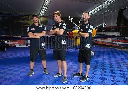 PUTRAJAYA, MALAYSIA - MAY 17, 2014: The team of Kirby Chambliss (USA) pose with their Edge 540 v3 plane in the hangar at the Red Bull Air Race World Championship 2014 in Putrajaya, Malaysia.