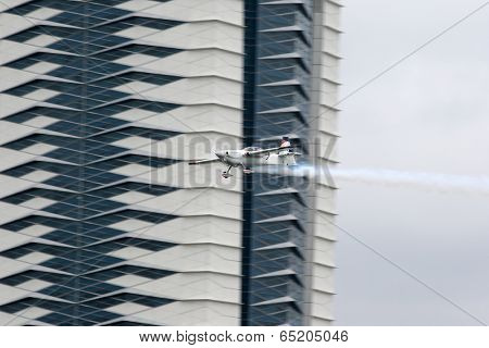 PUTRAJAYA, MALAYSIA - MAY 17, 2014: Matthias Dolderer of Germany, in an Edge 540 V3 plane flies by the skyscrapers of Putrajaya at the Red Bull Air Race World Championship 2014.
