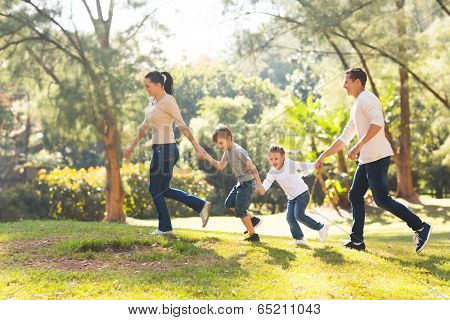 playful family hand in hand running in forest