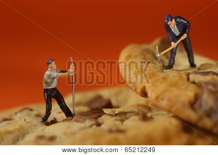 Miniature Plastic People Working on Chocolate Chip Cookies