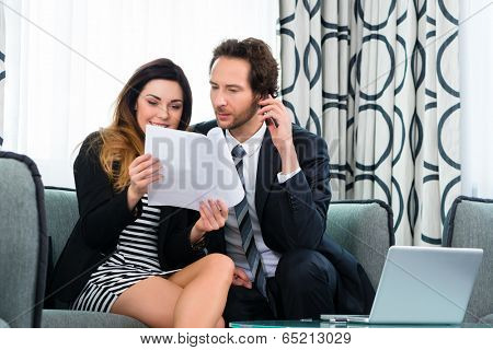 Businesspeople in a business hotel discussing some documents also on the phone, maybe they are working on a contract