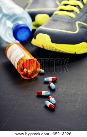 Different tools for sport and pills (Vitamins or Fitness Supplement) on grey background - sport, health and diet concept
