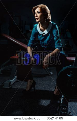 Portrait of beautiful young woman in a trouser suit doing exercise with dumbbells