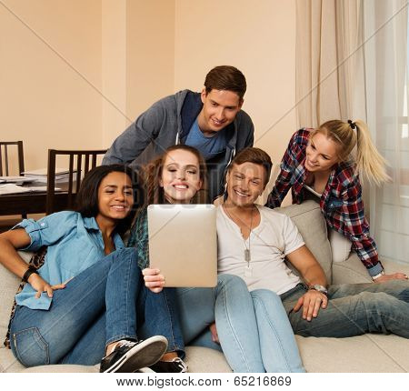 Group of young multi ethnic friends taking selfie in home interior