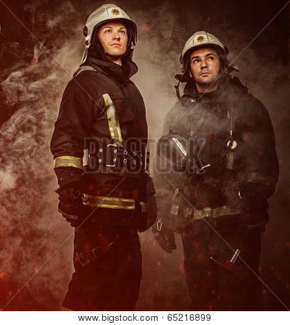 Two firefighters with helmet and axe in a smoke