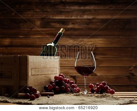 Bottle, glass and red grape on a wooden table