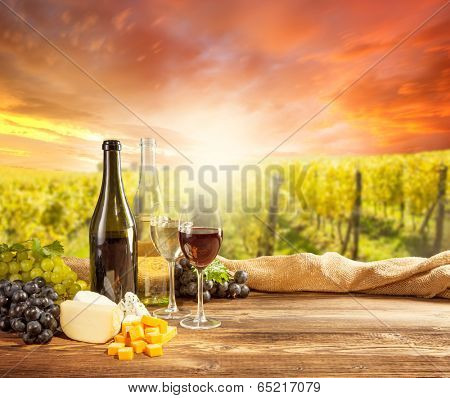 Wine still life with bottle and glass of red wine. Rural vineyard on background