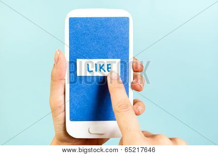 Push The Blue Like Button On The Phone Concept. Hand pushing like concept on a cell phone.