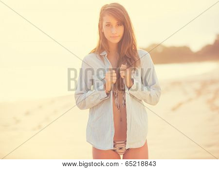 Fashion portrait, Beautiful woman on the beach at sunset. Backlit, warm sunny colors.