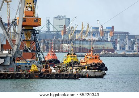 Tugboat and freight train under port crane