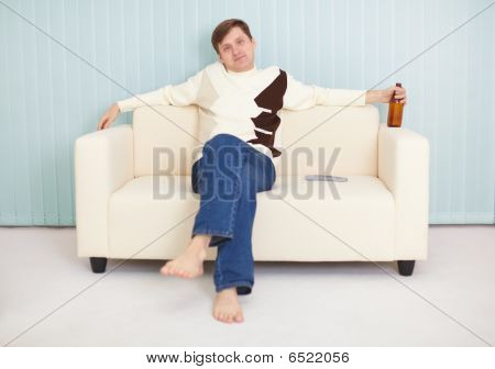 Young Guy Has Rest On A Sofa With Beer And Tv