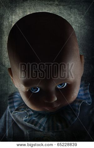 Creepy Looking Doll With Blue Eyes With Dramatic Lighting And Textured Background.