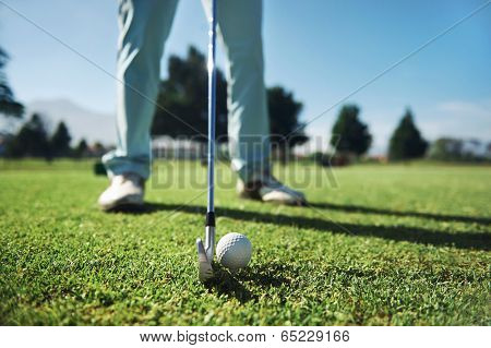 Closeup of golfer with iron hitting tee shot