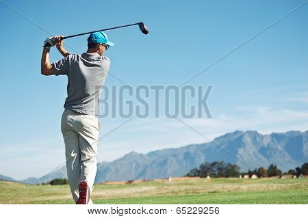 Golfer hitting tee shot with driver from teebox, on beautiful course and good strike
