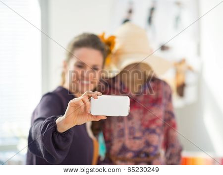 Closeup On Happy Fashion Designer Taking Self Photo With Garment