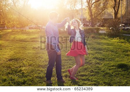 loving couple dancing in the park at sunset