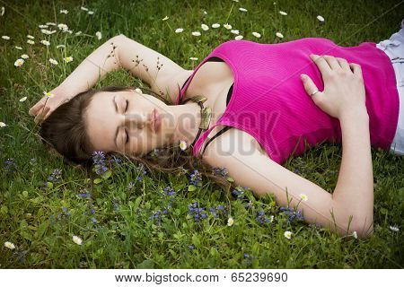 Attractive Young Woman Laying Down In Grassland