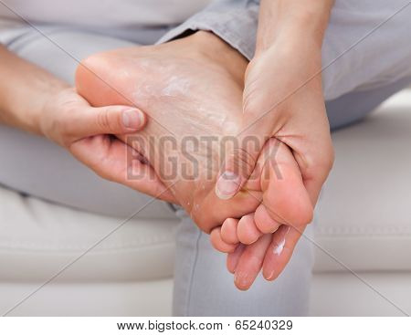 Woman Applying Cream On Feet