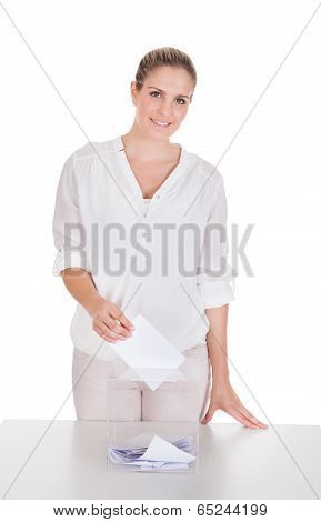 Woman Inserting Ballot In Box