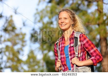 Young happy woman hiker hiking in forest. Smiling beautiful girl on hike looking enjoying view living healthy active aspirational outdoors lifestyle. Portrait of pretty blonde woman in her 20s.
